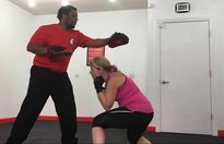 Boxing workout: Female ducking under punches. Male holding pads and throwing punches.